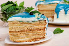 Stuk van cake met blauwe room, munt en bosbessen wordt verfraaid die Stock Afbeeldingen