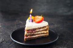 Stuk van cake van verjaardags de gezonde yougurt met verse bessen en brandende kaars op de zwarte plaat op donkergrijze, zwarte s Royalty-vrije Stock Foto's