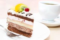 Stuk van chocoladecake met fruit op plaat Stock Foto's