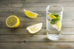 Stuk van citroen en muntblad in transparant glas mineraalwater met bellen op houten achtergrond royalty-vrije stock foto