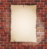 Stuk van document op bakstenen muur Royalty-vrije Stock Afbeelding