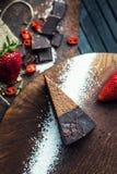 Stuk van donkere chocoladecake met aardbei De restaurant of koffieatmosfeer retro wijnoogst Stock Fotografie