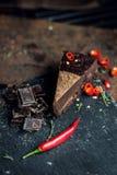 Stuk van donkere chocoladecake met roodgloeiende peper De restaurant of koffieatmosfeer retro wijnoogst Royalty-vrije Stock Foto's