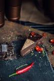 Stuk van donkere chocoladecake met roodgloeiende peper De restaurant of koffieatmosfeer retro wijnoogst Stock Fotografie