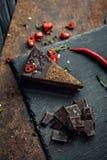 Stuk van donkere chocoladecake met roodgloeiende peper De restaurant of koffieatmosfeer retro wijnoogst Royalty-vrije Stock Afbeelding