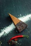 Stuk van donkere chocoladecake met roodgloeiende peper De restaurant of koffieatmosfeer retro wijnoogst Stock Afbeeldingen