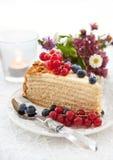 Stuk van eigengemaakte die honingscake met verse bessen wordt verfraaid Stock Afbeelding
