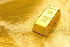 Stuk van gouden bar op gouden achtergrond royalty-vrije stock foto