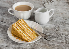 Stuk van honingscake en thee met melk Stock Foto