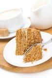 Stuk van honingscake op een plaat, een room en een cappuccino Stock Foto