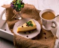 Stuk van kaastaart en koffie op een dienblad Stock Afbeeldingen