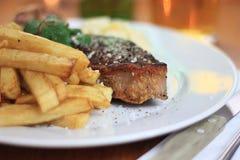 Stuk van lapje vlees met frietenclose-up Stock Fotografie