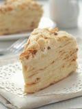 Stuk van multi gelaagd cakeclose-up Mille feuille dessert Verkruimelt verfraaid torte op witte doily op houten lijst stock fotografie