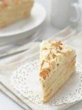 Stuk van multi gelaagd cakeclose-up Mille feuille dessert Verkruimelt verfraaid torte op witte doily op houten lijst royalty-vrije stock foto's