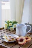 Stuk van perzikpastei op een witte plaat, witte mok met thee Stock Fotografie