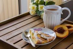 Stuk van perzikpastei op een witte plaat, witte mok met thee Royalty-vrije Stock Afbeelding