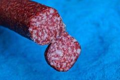 Stuk van rode salamiworst op blauwe achtergrond royalty-vrije stock afbeeldingen