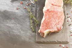 Stuk van ruw vlees van rundvlees op een leiraad met peper en thy Stock Afbeeldingen