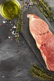 Stuk van ruw vlees van rundvlees op een leiraad met peper, olijf oi Stock Afbeelding