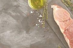 Stuk van ruw vlees van rundvlees op een leiraad met peper, olijf oi Stock Foto's
