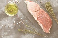 Stuk van ruw vlees van rundvlees op een leiraad met peper, olijf oi Stock Afbeeldingen