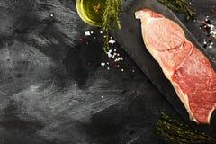 Stuk van ruw vlees van rundvlees op een leiraad met peper, olijfolie en een thyme op een donkere achtergrond Hoogste mening, exem Stock Foto's