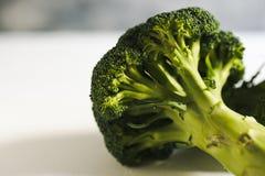 Stuk van ruwe broccoli op wit hout Stock Afbeelding