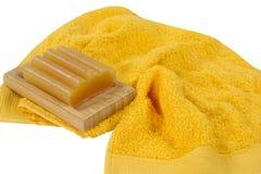 Stuk van zeep en een gele die handdoek op witte achtergrond wordt geïsoleerd stock afbeelding