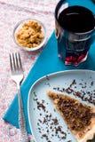 Stuk van zoete cake met karamel en chocolade en een glas Stock Foto's