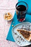 Stuk van zoete cake met karamel en chocolade en een glas Stock Afbeeldingen