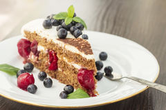 Stuk van zoete cake met kers, bosbes en munt Stock Afbeelding