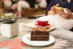Stuk van zoete macadamia chocoladecake met kop van koffie Stock Fotografie