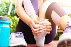 Stukad ankel Lidande för ung kvinna från en ankelskada, medan öva och köra Sjukvård- och sportbegrepp royaltyfri bild