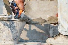 Stukadoor concrete arbeider bij muur van huisbouw royalty-vrije stock afbeeldingen