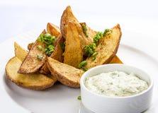 Stukken aardappelen in de schil met saus stock foto's