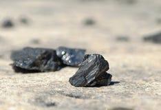 Stukken die van steenkool op de weg liggen Stock Afbeelding