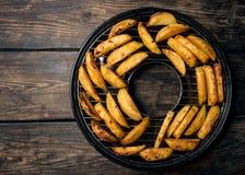 Stukken gebraden aardappels op een grill Stock Foto's