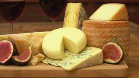 Stukken kaas en fig. op een houten lijst stock footage
