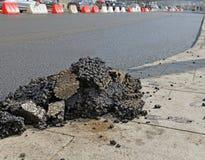 Stukken van asfalt dichtbij hersteld weg stock foto