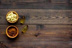 Stukken van cacaoboter en cacaopoeder in kom voor eigengemaakte schoonheidsmiddelen De donkere houten ruimte van het achtergrond  Stock Afbeeldingen