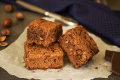 Stukken van cake op perkament, hazelnoot en chocolade Stock Afbeelding
