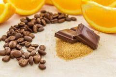Stukken van chocolade op bruine die suiker, door oranje plakken worden omringd Royalty-vrije Stock Foto
