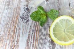 Stukken van citroen met ijsblokjes op een oud houten lijstclose-up Gesneden citroen met munt het concept frisdranken royalty-vrije stock fotografie