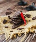 Stukken van donkere chocolade met Spaanse pepers op zwarte steenkoolraad Royalty-vrije Stock Afbeeldingen