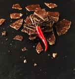 Stukken van donkere chocolade met Spaanse pepers op zwarte steenkoolraad Royalty-vrije Stock Fotografie