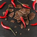 Stukken van donkere chocolade met Spaanse pepers op zwarte steenkoolraad Stock Afbeelding