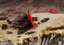Stukken van donkere chocolade met Spaanse pepers op zwarte steenkoolraad Stock Foto