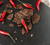 Stukken van donkere chocolade met Spaanse pepers op zwarte steenkoolraad Royalty-vrije Stock Foto