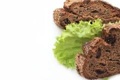 Stukken van eigengemaakt roggebrood met Amerikaanse veenbessen en slabladeren op een witte achtergrond voor adreskaartje royalty-vrije stock foto's
