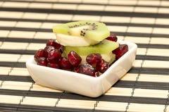 Stukken van fruitbanaan, kiwi, granaatappel in kleine schotel Stock Afbeeldingen